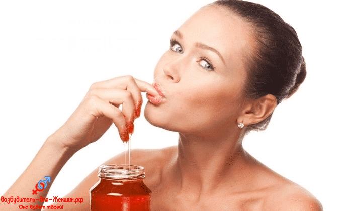 Красивая девушка ест мед