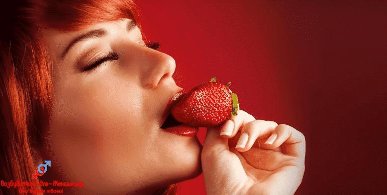 Рыжая девушка кусает клубнику