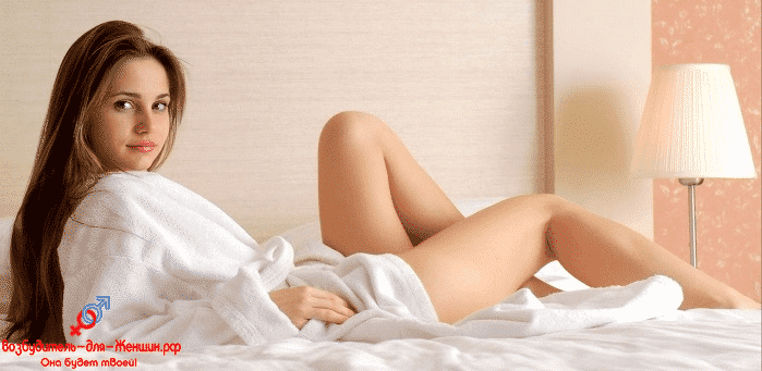 Девушка в белом махровом халате на кровати