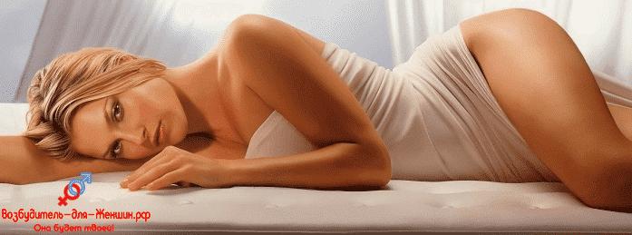 Девушка в простыне лежит на кровати