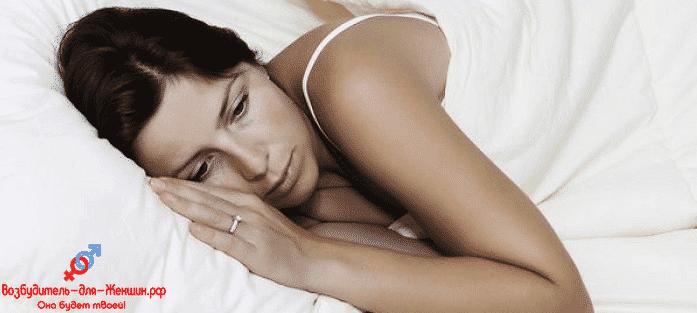 Грустная женщина лежит на кровати