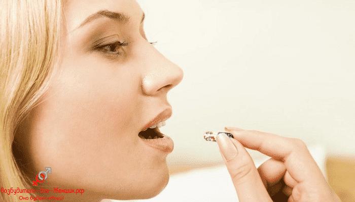 Блондинка принимает большую таблетку