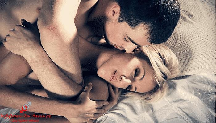 Брюнет целует блондинку на кровати