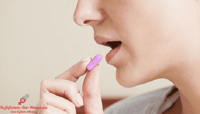 Девушка подносит таблетку ко рту