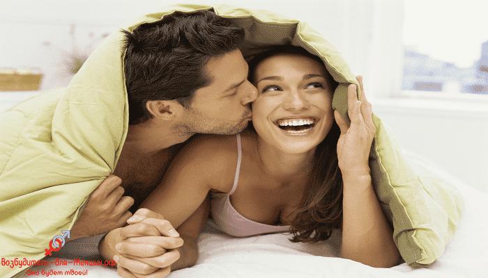Мужчина целует девушку под одеялом